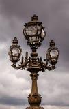 Gatalykta på den Alexandre III bron mot molnig himmel Arkivbilder