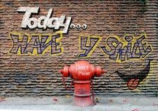 Gatamålarfärg på väggen och vattenposten arkivfoton