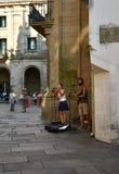 Gatamusiker som framme utför av domkyrkan Platerias fyrkant med turister, Santiago de Compostela, Spanien fotografering för bildbyråer