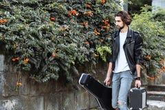 Gatamusiker som rymmer ett fall med en gitarr och en förstärkare r Spela som gör pengar en uppehälle ( fotografering för bildbyråer