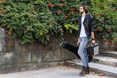 Gatamusiker som rymmer ett fall med en gitarr och en förstärkare r Spela som gör pengar en uppehälle ( arkivbilder