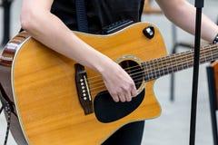 Gatamusiker som spelar den akustiska gitarren utomhus arkivfoto