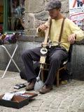 Gatamusiker som spelar det konstiga randiga instrumentet royaltyfri fotografi