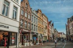 Gatan med folk, tegelstenhus och shoppar på Bruges Arkivfoton