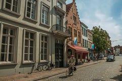 Gatan med folk, tegelstenhus och shoppar på Bruges Arkivbilder
