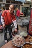 Gatan som ler kocken, säljer varm mat på ett smalt stycke Royaltyfri Bild