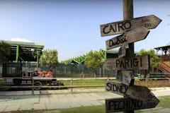 Gatan undertecknar det naturligt parkerar in att indikera riktningar till olika ställen av världen En lokomotiv på bakgrunden royaltyfri bild