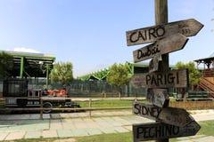Gatan undertecknar det naturligt parkerar in att indikera riktningar till olika ställen av världen En lokomotiv på bakgrunden royaltyfri foto
