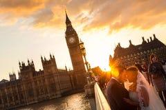 Gataplats av slumpmässigt folk på den Westminster bron i solnedgång, London, UK Royaltyfri Fotografi