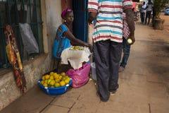 Gataplats i staden av Bissau med en kvinna som säljer apelsiner, i Guinea-Bissau, Västafrika royaltyfria bilder