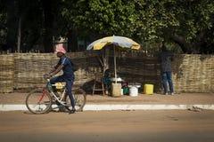 Gataplatsen i staden av Bissau med en kvinna som säljer frukt och två, man, i Guinea-Bissau royaltyfria foton