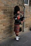 Gatasäckpipeblåsaren i stadsEdinburg i Skottland fotografering för bildbyråer