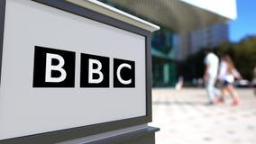 Gatasignagebräde med brittisk radio- och televisionsbolagetBBClogo Suddig kontorsmitt och gå folkbakgrund arkivfoto