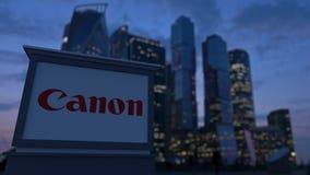 Gatasignagebräde med Canon Inc logo i aftonen Suddig bakgrund för skyskrapor för affärsområde Ledare 3 Royaltyfri Bild