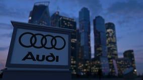 Gatasignagebräde med den Audi logoen i aftonen Suddig bakgrund för skyskrapor för affärsområde Ledare 3 Royaltyfri Fotografi