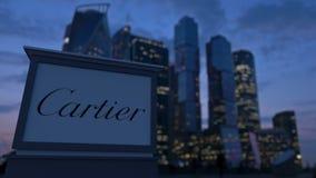 Gatasignagebräde med den Cartier logoen i aftonen Suddig bakgrund för skyskrapor för affärsområde Ledare 3 Arkivfoto