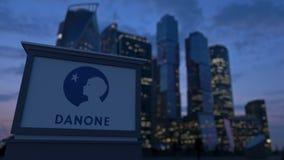 Gatasignagebräde med den Danone logoen i aftonen Suddig bakgrund för skyskrapor för affärsområde Ledare 3 Royaltyfri Foto