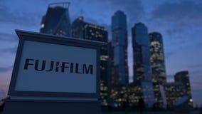Gatasignagebräde med den Fujifilm logoen i aftonen Suddig bakgrund för skyskrapor för affärsområde Ledare 3 Arkivbild