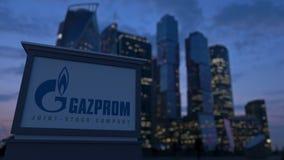 Gatasignagebräde med den Gazprom logoen i aftonen Suddig bakgrund för skyskrapor för affärsområde Ledare 3 Arkivfoto