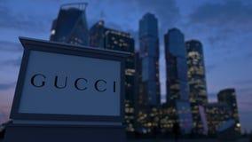 Gatasignagebräde med den Gucci logoen i aftonen Suddig bakgrund för skyskrapor för affärsområde Ledare 3 Royaltyfria Foton