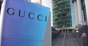 Gatasignagebräde med den Gucci logoen Modern kontorsmittskyskrapa och trappabakgrund Redaktörs- tolkning 3D Royaltyfri Foto