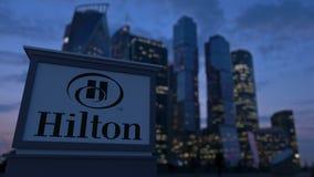 Gatasignagebräde med den Hilton Hotels Resorts logoen i aftonen Suddig backgroun för skyskrapor för affärsområde Arkivbilder