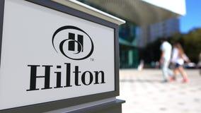Gatasignagebräde med den Hilton Hotels Resorts logoen Suddig kontorsmitt och gå folkbakgrund Ledare 3D fotografering för bildbyråer