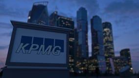Gatasignagebräde med den KPMG logoen i aftonen Suddig bakgrund för skyskrapor för affärsområde Ledare 3 Arkivbilder