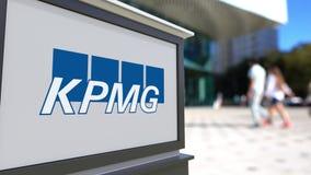 Gatasignagebräde med den KPMG logoen Suddig kontorsmitt och gå folkbakgrund Redaktörs- tolkning 3D royaltyfri bild