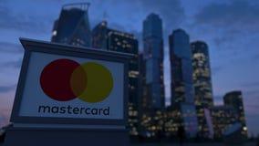Gatasignagebräde med den MasterCard logoen i aftonen Suddig bakgrund för skyskrapor för affärsområde Ledare 3 Arkivbild