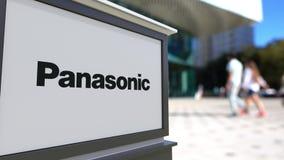 Gatasignagebräde med den Panasonic Korporation logoen Suddig kontorsmitt och gå folkbakgrund Ledare 3D Arkivfoto