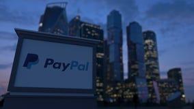 Gatasignagebräde med den Paypal logoen i aftonen Suddig bakgrund för skyskrapor för affärsområde Ledare 3 Royaltyfri Fotografi