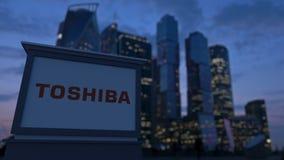 Gatasignagebräde med den Toshiba Corporation logoen i aftonen Suddig backgroun för skyskrapor för affärsområde Arkivfoton