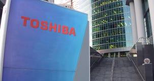 Gatasignagebräde med den Toshiba Corporation logoen Modern kontorsmittskyskrapa och trappabakgrund Ledare 3D Royaltyfri Foto