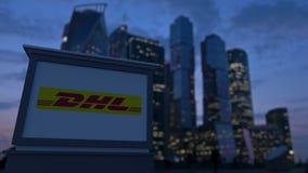 Gatasignagebräde med DHL den uttryckliga logoen i aftonen Suddig bakgrund för skyskrapor för affärsområde Editoria Royaltyfria Foton