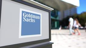 Gatasignagebräde med Goldman Sachs Group, Inc logo Suddig kontorsmitt och gå folkbakgrund Royaltyfria Bilder