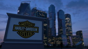 Gatasignagebräde med Harley-Davidson, Inc logo i aftonen Suddig backgroun för skyskrapor för affärsområde Arkivbild