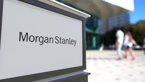 Gatasignagebräde med Morgan Stanley Inc logo Suddig kontorsmitt och gå folkbakgrund Ledare 3D Arkivbilder