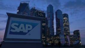 Gatasignagebräde med SAP SE-logo i aftonen Suddig bakgrund för skyskrapor för affärsområde Ledare 3 Royaltyfri Bild