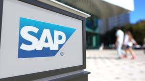 Gatasignagebräde med SAP SE-logo Suddig kontorsmitt och gå folkbakgrund Redaktörs- tolkning 3D Royaltyfri Foto