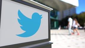 Gatasignagebräde med Twitter, Inc logo Suddig kontorsmitt och gå folkbakgrund Ledare 3D Royaltyfri Fotografi