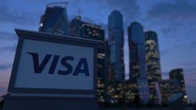 Gatasignagebräde med visumet Inc logo i aftonen Suddig bakgrund för skyskrapor för affärsområde Ledare 3 Royaltyfri Bild