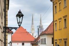 Gatasikt av domkyrkatornen över taken i Zagreb, Kroatien royaltyfri foto