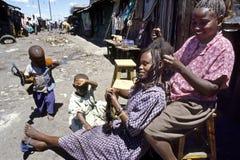 Gatasikt av frisören och kunden i slumkvarteret arkivbild