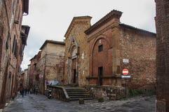 Gatasikt och medeltida byggnader i en molnig dag i Siena Arkivfoton