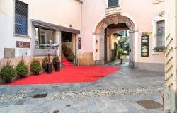Gatasikten med den moderiktiga coctailstången dekorerade med röd matta i den historiska mitten av Varese Royaltyfri Fotografi