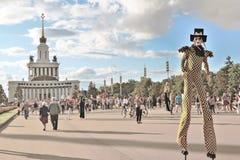 Gataskådespelaren på styltor poserar för foto i Moskva Arkivbild