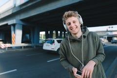 Gataståenden av en lycklig ung man, som ler, och lyssnar till en musiker i hörlurar i bakgrunden av stads- arkitektur Arkivfoton