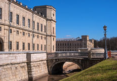 Gatchina Palace. Russia. The left wing of the palace in the foreground. Water ditch and a bridge through it. Stock Photos