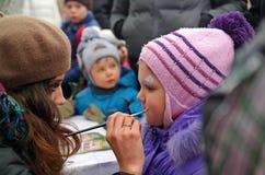 Gatchina, región de Leningrad, RUSIA - 2 de marzo de 2014: Muchacha que hace un maquillaje de los niños, quizás es el gato Imágenes de archivo libres de regalías